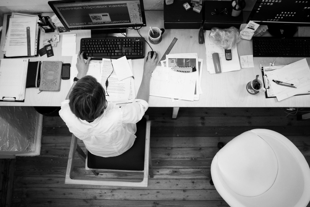 Widok z góry na biurko, komputer i pracownika.