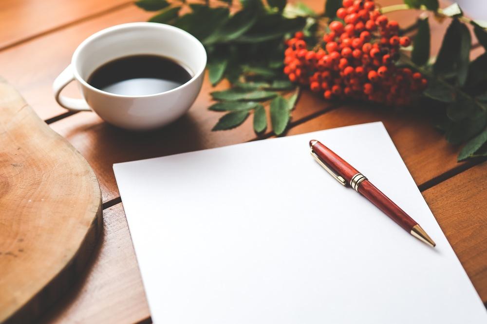 Zbliżenie na stół, na nim kawa, pusta kartka z długopisem i jarzębina.